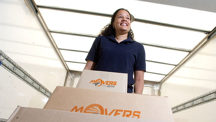 Woman providing top class moving services NYC has, and carrying boxes