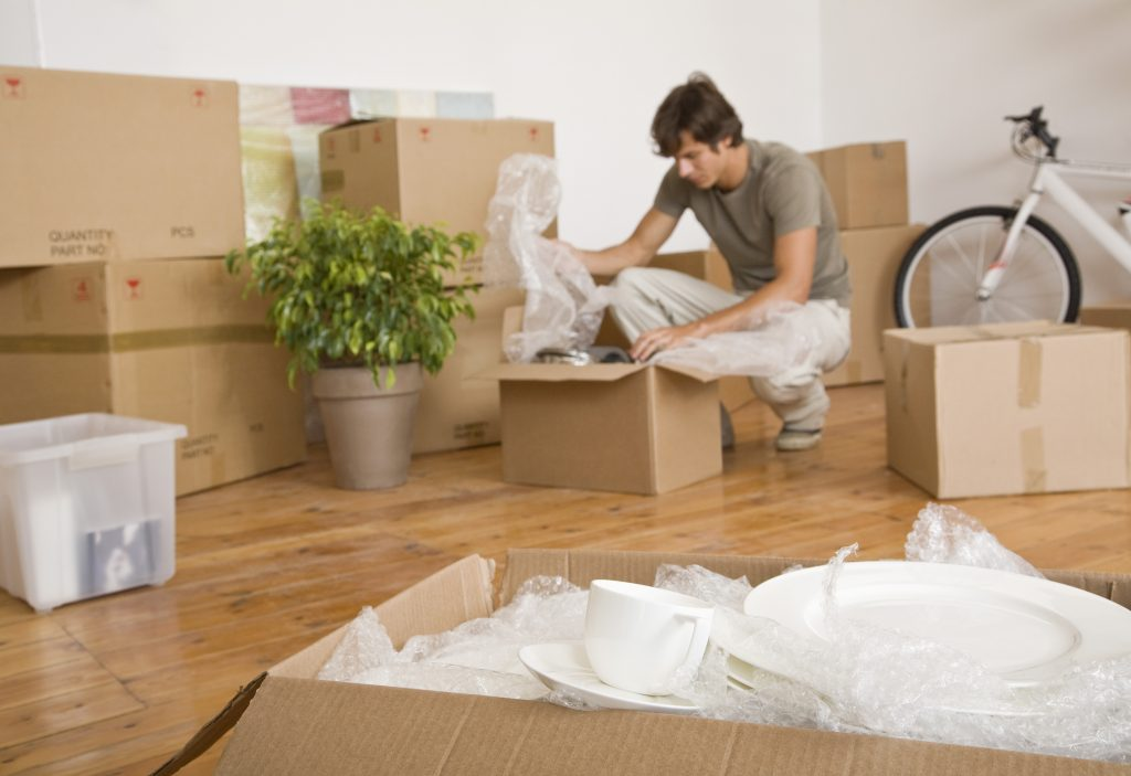 Man unpacking moving boxes after Brooklyn local movers have left
