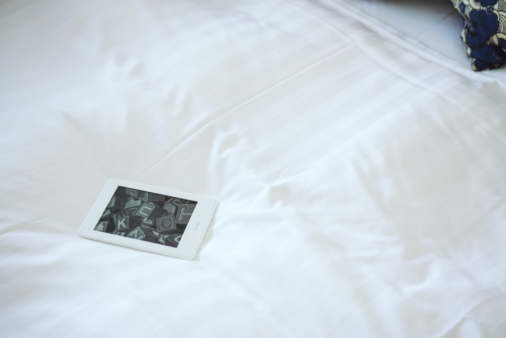 Kindle on standby on a bed.