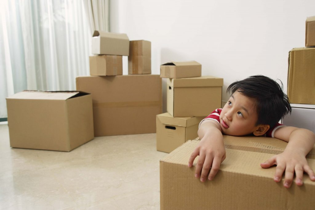 Boy surrounded by moving boxes.