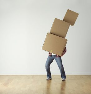 A man carrying a stack of moving boxes.