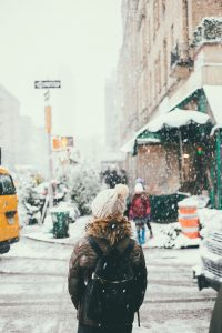 Woman wearing a white hat in NYC streets during a blizzard