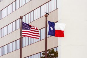 Texas and US flags on poles next to each other.
