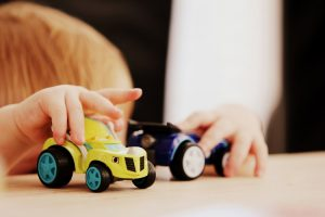 Child playing with toy cars.