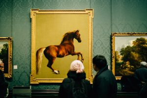 a painting of a horse in a museum and two people observing it
