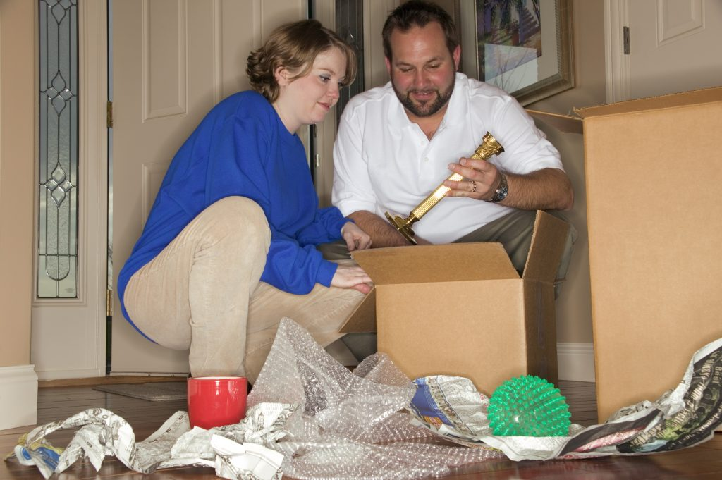 couple packing boxes for a moving on a deadline
