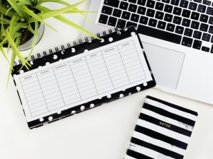 black and white timetable notebook on white laptop