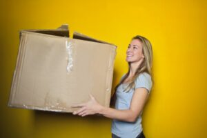 A woman carrying a large moving box